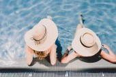 overhead view of two women in straw hats relaxing in swimming pool