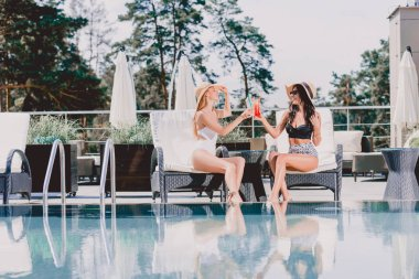 sexy brunette and blonde women in swimsuits drinking cocktails near swimming pool
