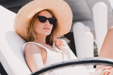 Beautiful blonde woman in straw hat and sunglasses sunbathing on lounger stock vector
