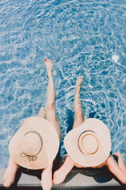 Top view of two women in straw hats relaxing in swimming pool stock vector