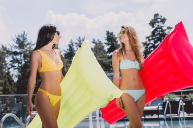 low angle view of happy blonde and brunette girls in swimsuits and sunglasses walking with inflatable pool floats and looking at each other