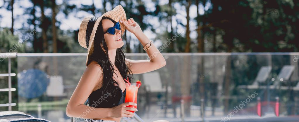 beautiful brunette young woman in swimsuit, straw hat and sunglasses smiling while holding cocktail, panoramic shot