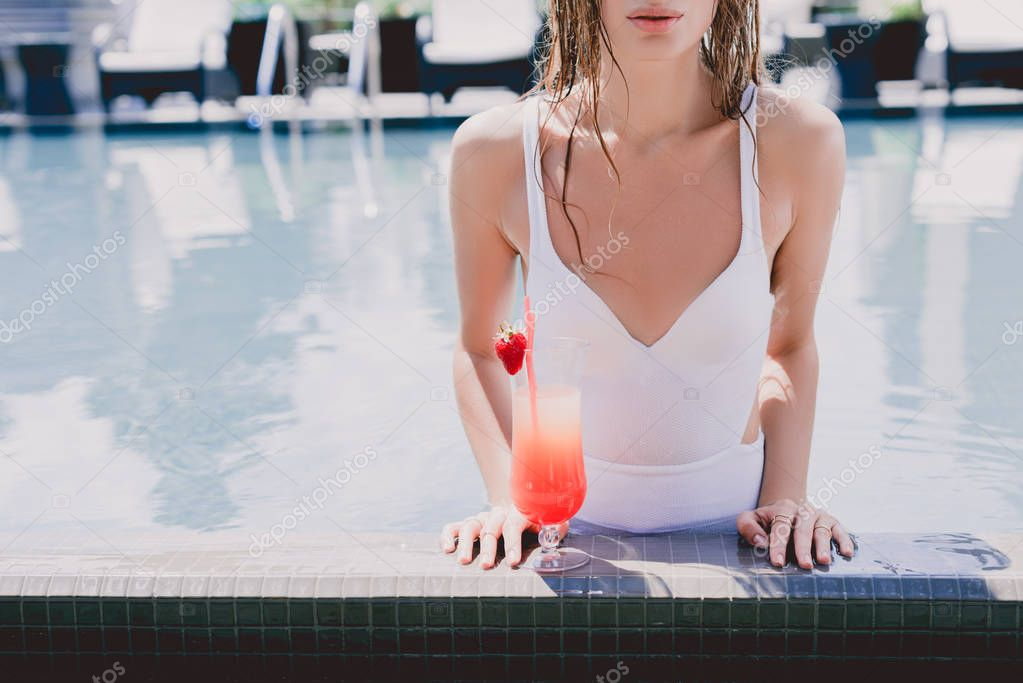 cropped view of wet woman in swimming pool with cool strawberry cocktail