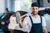 šťastný automobilový mechanik v lahvích s automobilovou naftou