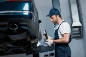 célzott hangsúly a csinos autószerelő gazdaság fémes részletek közelében Automobile