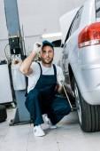 szakállas autószerelő egyenruhás sapkával, az autó autógumik autószervizben való