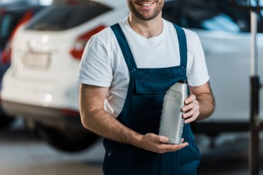 Cropped view of cheerful car mechanic holding bottle with car oil stock vector