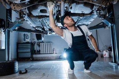 Handsome auto mechanic in cap repairing automobile in car service stock vector