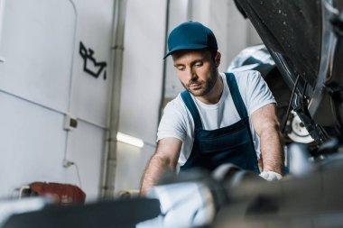 Selective focus of handsome car mechanic fixing car stock vector