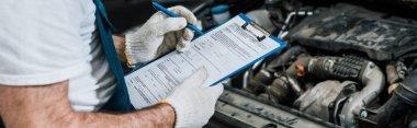 Panoramic shot of repairman holding pen and clipboard near car stock vector