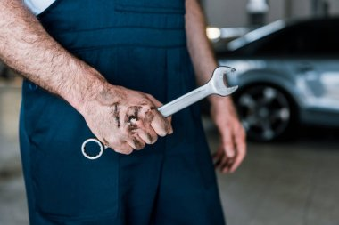 cropped view of auto mechanic with mud on hand holding hand wrench in car repair station