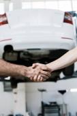 oříznutý pohled na auto mechanika se třesou rukou muž v garáži