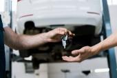 oříznutý pohled automatického mechanika na klíč k člověku v garáži