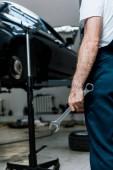 oříznutý pohled na opravárník přidržujte ruční klíč na opravě auta