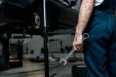 oříznutý pohled na auto mechanika přidržujte klíč na opravě auta