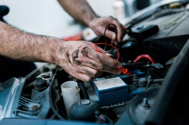 cropped view auto mechanic with mud on hands fixing automobile in car repair station