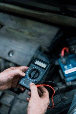 cropped view of auto mechanic holding measuring device in car service