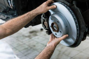 Cropped view of car mechanic holding metallic car brake near automobile stock vector
