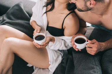 cropped view of woman in bra and man holding cups with coffee