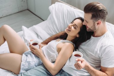 attractive and brunette woman and man holding cups, lying on bed and hugging
