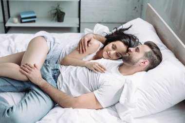 attractive and brunette woman and man with closed eyes hugging and sleeping