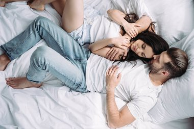 top view of attractive woman and man with closed eyes hugging and sleeping