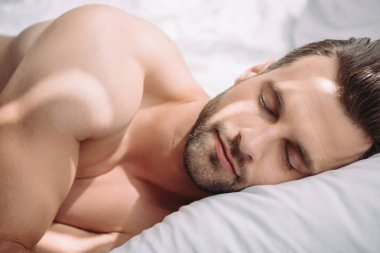handsome and shirtless man with closed eyes sleeping in bed