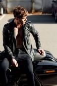 mladý motocyklista sedící na motorce a s pohledem stranou
