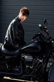 mladý motocyklista v černé kožené bundě sedící na motocyklu