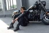 mladý muž sedící u černé motorky a držící cigaretu