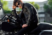 Úplná délka pohledu na neširo motocyklista stojící poblíž motocyklu vně a s pohledem stranou