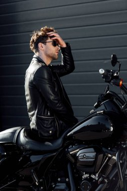 handsome young man sitting on motorcycle and readjusting hair