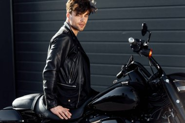 handsome young man in leather jacket sitting on black motorcycle