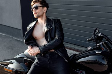 muscular young man in leather jacked leaning on motorcycle