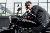 pohledný mladý muž v kožené bundě, který odpočívá při sezení na novém černém motocyklu