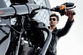 pohled nízkého úhlu pohledu na rukojeť s oranžovým světlem a mužem v kožené bundě sedící na motocyklu