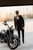 pohledný mladý muž, který chodí do garáže na černý motocykl
