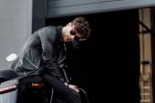 mladý motocyklista v brýlích a kožené bundě při sezení na motorce blízko garáže