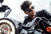 selektivní zaměření lampy na osvětlení a pohledného muže, který sedí na motorce a dívá se jinam