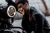 pohledný mladý muž, který se opírá o motocykl a usmíval se při pohledu na lampu