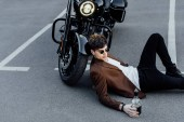 pohledný muž držící láhev s alkoholem a přitom ležet na zemi a naklánět hlavu na kole motocyklu