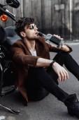 mladý muž konzumace alkoholu při sezení na zemi u motocyklu