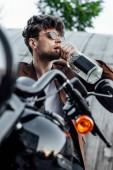 szelektív középpontjában a jóképű ember iszik alkoholt ülve a motorkerékpár-és néz el