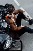 Fotografie pohled s vysokým úhlem pohledu na pohledného muže, který sedí na gordu u nového motocyklu a držící láhev