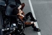 pohled na muže v brýlích a skafandru na zemi blízko motocyklu