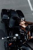mladý muž v brýlích a hnědém saku odpočívá při sezení na zemi a na motorce