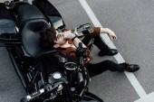 pohled na mladého motocyklista na zemi, opíraje se o motocykl a konzumní alkohol