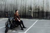 Fotografie pohled plný pohledného muže ve svěrací kazajce, který odpočívá na černém motocyklu a dívá se jinam