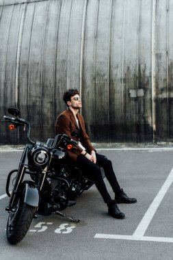 full length view of motorcyclist ion brown jacket sitting on motorcycle, resting and looking away