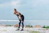 attractive and tired sportive woman standing on beach near sea